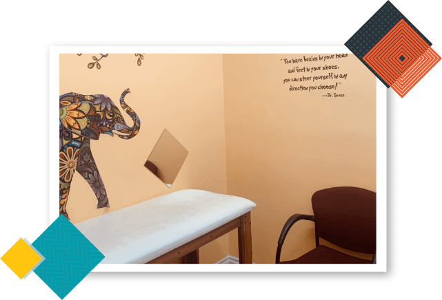 California Kids Pediatrics Clinic Care Unit with an elephant painting on the wall, pediatric examination table, and maroon-colored chair.