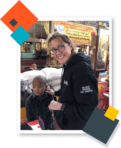 Dr. Marna Geisler wearing black pullover holds a toddler during her peace corps volunteer work.